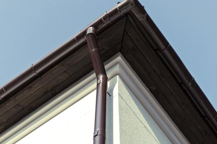 Montaje de conducto de drenaje pluvial en el lateral de la fachada de la casa